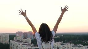 Het meisje heft omhoog haar handen op het dak van een huis op stock footage