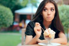 Het meisje Heisting aan eet het Hoge Dessert van het Calorieroomijs stock fotografie