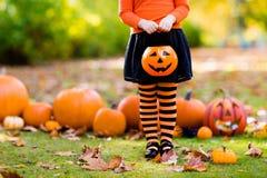 Het meisje in heksenkostuum op Halloween-truc of behandelt stock afbeelding