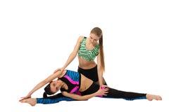 Het meisje helpt haar vriend die uitrekkende oefening doen Stock Foto