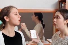 Het meisje herhaalt voor therapeut correcte audiouitspraak royalty-vrije stock afbeeldingen