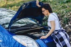 het meisje herstelt auto met een open kap op weg stock fotografie