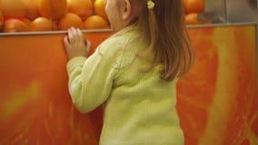 Het meisje het blonde in een anticiperen van het sap van sinaasappelen stock footage