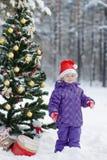 Het meisje in het hout dichtbij de verfraaide Kerstboom stock afbeelding