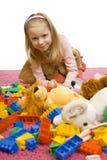 Het meisje in het midden van speelgoed-knoeit stock foto