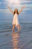 Het meisje in het overzees bij zonsondergang zegt vaarwel aan de zon royalty-vrije stock afbeeldingen