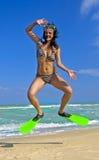 Het meisje in het zwemmen maskeert en vinnen springend bij een strand Stock Afbeeldingen