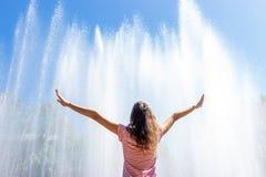 Het meisje hief haar op indient de achtergrond van de fontein en voelt vrijheid stock foto's