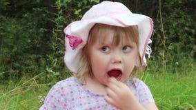 Het meisje in hoed eet onder gras stock videobeelden