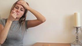 Het meisje hoest en meet de temperatuur stock videobeelden