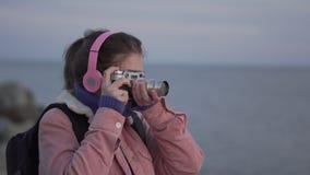 Het meisje in hoofdtelefoons neemt een beeld van de overzeese zonsondergang op haar uitstekende camera stock videobeelden