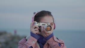 Het meisje in hoofdtelefoons neemt een beeld van de overzeese zonsondergang op haar uitstekende camera stock video