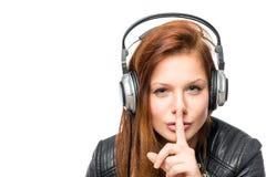 Het meisje in hoofdtelefoons vraagt levensonderhoud stil op een witte achtergrond royalty-vrije stock afbeelding