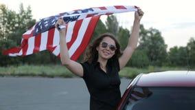 Het meisje houdt de banner van Amerika stock video