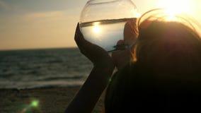 Het meisje houdt in de handen van een rond aquarium en bekijkt in openlucht de huisdierenvissen zonsondergang op kust dichte omho stock video