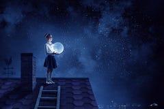Het meisje houdt de maan Gemengde media stock foto