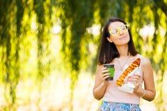 Het meisje houdt document kop van koffie in handen en eet pizza Stock Foto's