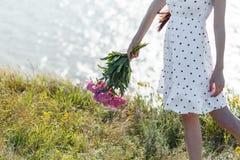 Het meisje houdt een boeket van mooie bloeiende roze pioenen Haar witte kleding fladdert in de wind Mooie de zomermening van t stock afbeeldingen