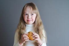 Het meisje houdt een broodje in hand Stock Afbeelding