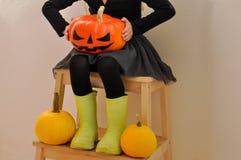 Het meisje houdt een enge die pompoen voor Halloween, zittend op een bank door andere pompoenen wordt omringd Closup stock fotografie