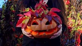 Het meisje houdt een gesneden pompoen waarvan de rode bladeren uitpuilen Halloween-pompoensymbool stock videobeelden