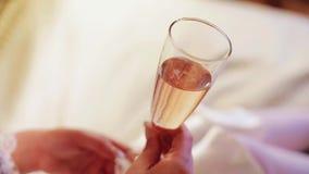 Het meisje houdt een glas champagne Sluit omhoog In de glas zichtbare bellen van gassen stock video