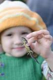 Het meisje houdt een hagedis Stock Foto