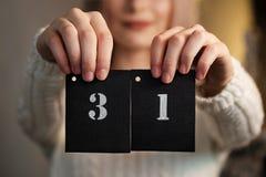 Het meisje houdt een kalenderblad 31 van December Nieuwjaar` s Vooravond stock foto
