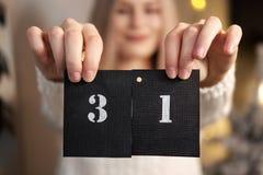Het meisje houdt een kalenderblad 31 van December Nieuwjaar` s Vooravond royalty-vrije stock afbeeldingen