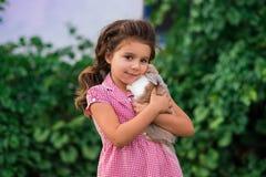 Het meisje houdt een leuk klein konijn, openluchtspruit stock afbeeldingen
