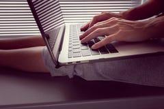 Het meisje houdt een MacBook Pro-Retina op haar overlapping en iets drukt stock foto