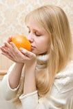 Het meisje houdt een sinaasappel stock afbeeldingen