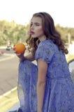 Het meisje houdt een sinaasappel in haar handen stock afbeeldingen