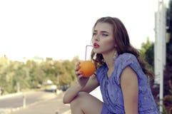 Het meisje houdt een sinaasappel in haar handen stock afbeelding
