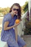 Het meisje houdt een sinaasappel in haar handen royalty-vrije stock afbeelding