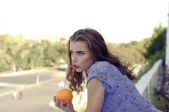 Het meisje houdt een sinaasappel in haar handen royalty-vrije stock foto's