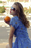 Het meisje houdt een sinaasappel in haar handen royalty-vrije stock foto
