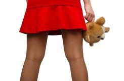 Het meisje houdt een stuk speelgoed in de hand Vrouwen` s heupen stock afbeelding