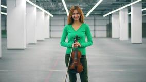 Het meisje houdt een viool in handen en glimlacht bij een camera stock videobeelden