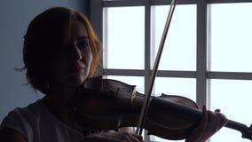 Het meisje houdt een viool op het door vingertechniek de snaren met een boog tegen het venster speelt Silhouet stock footage