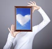 Het meisje houdt frame met wolken binnen hart Stock Foto