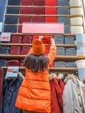 Het meisje houdt haar hand voor kleren op de opslagplank stand de klant trekt op een ding in een kledingsopslag Achtermening van stock fotografie