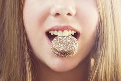 het meisje houdt haar tanden met koekjes, eet stock fotografie