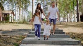 Het meisje houdt handen van haar babybroer, die samen op steentrede lopen in een park in dag, zijn de ouders stock videobeelden