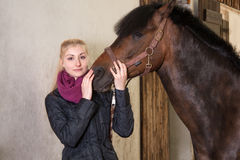 Het meisje houdt het hoofd van haar poney Royalty-vrije Stock Foto's