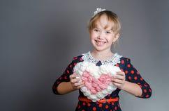 Het meisje houdt met handenhart en lacht Stock Foto's