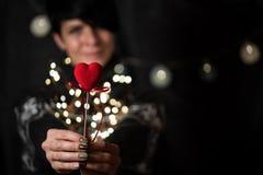 Het meisje houdt rood hart op een bokehachtergrond in hand royalty-vrije stock foto's
