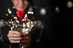 Het meisje houdt rood hart op een bokehachtergrond in hand stock afbeeldingen