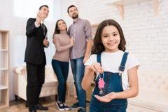 Het meisje houdt sleutels aan huis terwijl de makelaar in onroerend goed flats aan jong paar toont royalty-vrije stock foto's