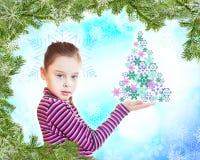 Het meisje houdt spar tegen feestelijke Nieuwjaarachtergrond Stock Afbeeldingen